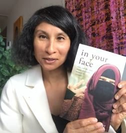 Natasha Bakht holding a copy of her book, In Your Face. She has a medium skin tone and black hair, and she is wearing a white blazer.