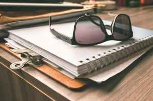 black frame wayfarer sunglasses on white notebook