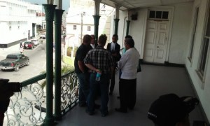 Rice importer, Jack Charles backing camera (with bottle in hand) and lawyers outside the Belize High Court room.