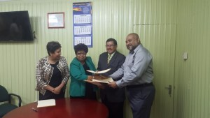 Ministers Amna Ally and Sydney Allicock and Dr. Suresh Narine exchanging copies of the MoU while Minister within the Ministry of Indigenous People's Affairs, Ms. Valerie Garrido-Lowe looks on.