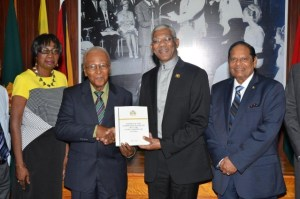 Chairperson of the Public Service Commission of Inquiry, Professor Harold Lutchman presents the Report to President David Granger, in the presence of Commissioners Ms. Sandra Jones and Prime Minister Moses Nagamootoo