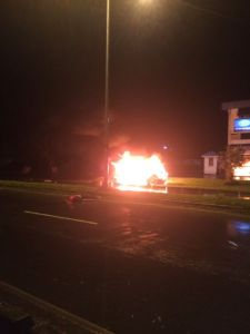 The burning car in which Bashment was travelling. In the foreground is his body.
