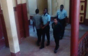 Philbert 'Phil Phil' Edwards being escorted out of court by police.