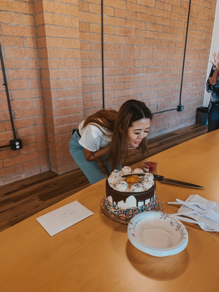Demi Bang blowing out a scented candle instead of a birthday candle.