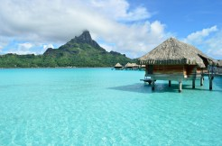 Luxury overwater bungalow in a vacation resort in the clear blue lagoon with a view on the tropical island of Bora Bora, near Tahiti, in French Polynesia.