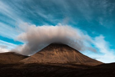 Iceland. The afternoon sun set on the well known Cone Shaped Mountain in Iceland as the cloud lifted to the peak.