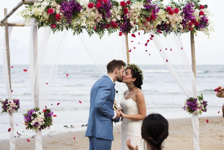 Cérémonie sur la plage, les mariés s'embrassent.