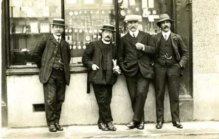 Four gentlemen in suits & hats in front of a shop window in Corwen c.1920, PPD/105/56