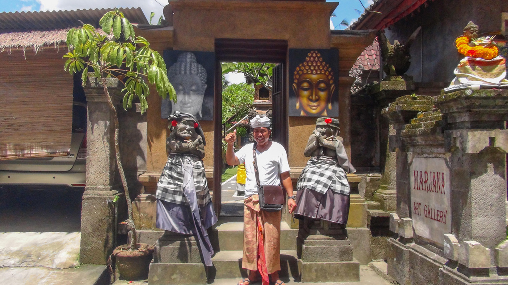 The artist in front of his art gallery, which is in a traditional Bali house.