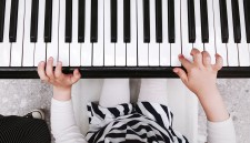 Closeup of child's hands playing the piano