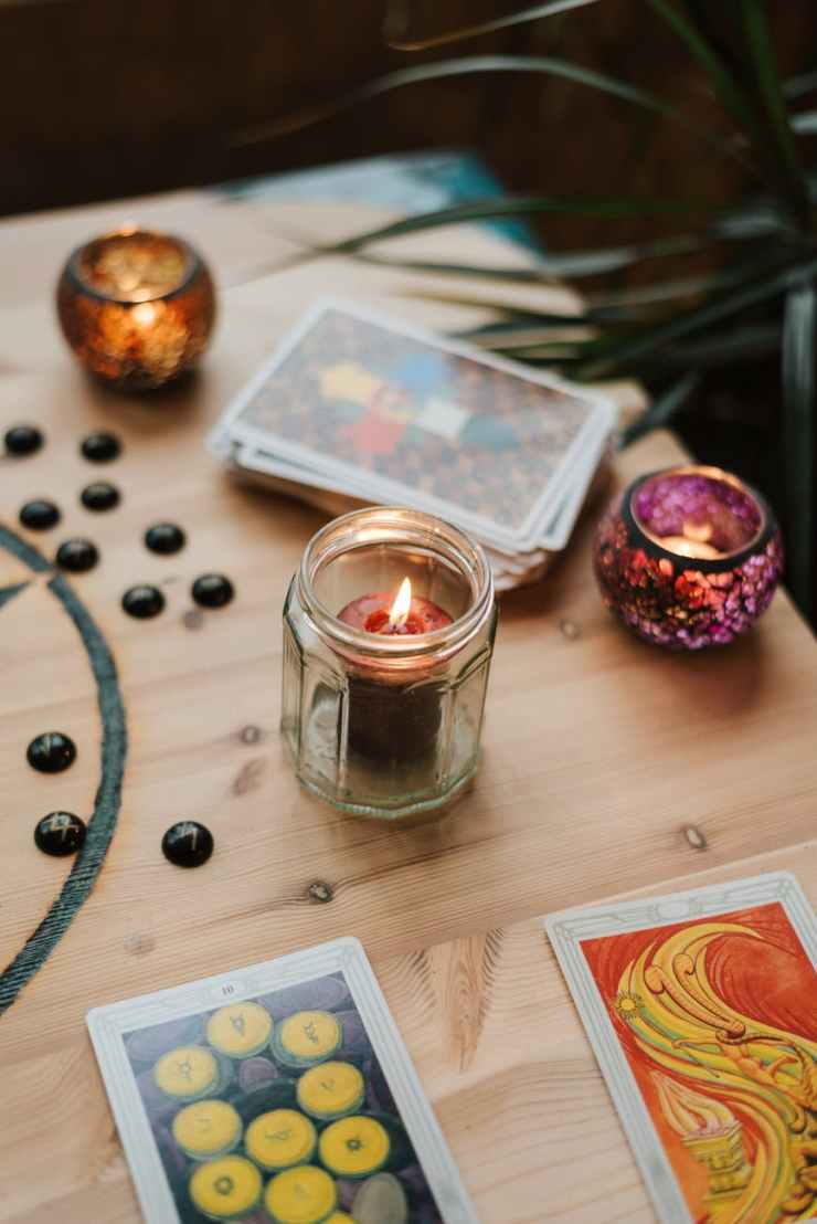 burning candles near tarot cards on table