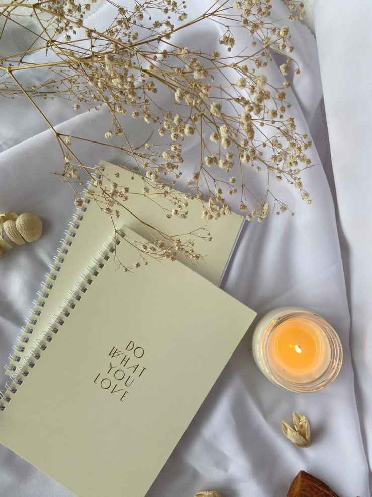 spiral notebooks placed on white cloth with burning candle