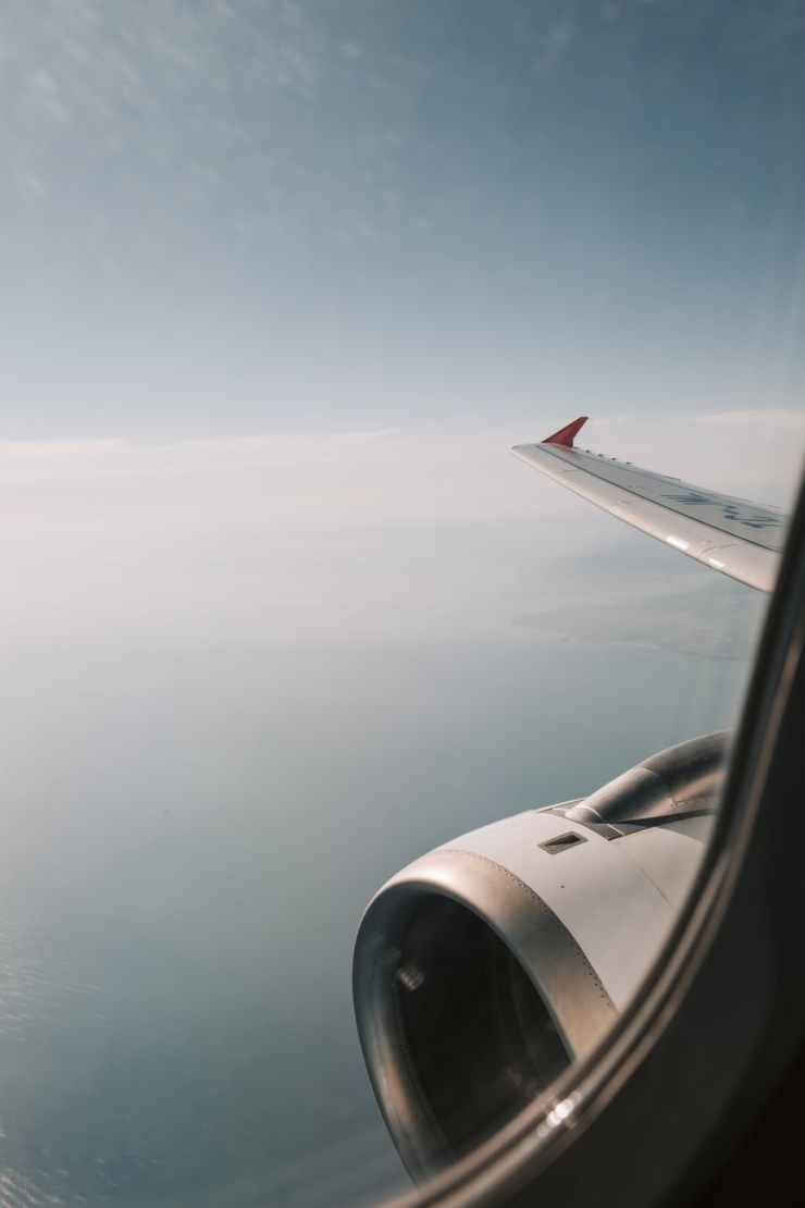 view of white airplane wing over the clouds