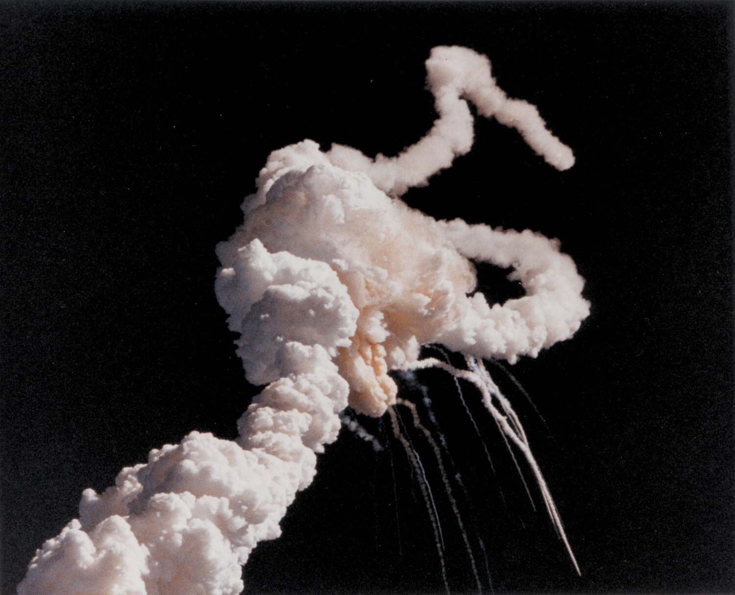 "Bild: ""On January 28, 1986, the Space Shuttle Challenger and her seven-member crew were lost when a ruptured O-ring in the right Solid Rocket Booster caused an explosion soon after launch. This photograph, taken a few seconds after the accident, shows the Space Shuttle Main Engines and Solid Rocket Booster exhaust plumes entwined around a ball of gas from the External Tank. Because shuttle launches had become almost routine after fifty successful missions, those watching the shuttle launch in person and on television found the sight of the explosion especially shocking and difficult to believe until NASA confirmed the accident."""