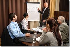 Business man at team meeting point flip-chart