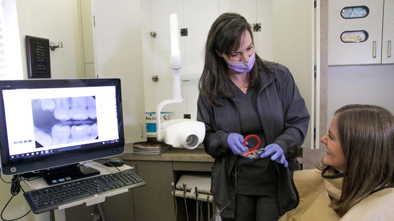 Happy patient receiving dental sensor treatment