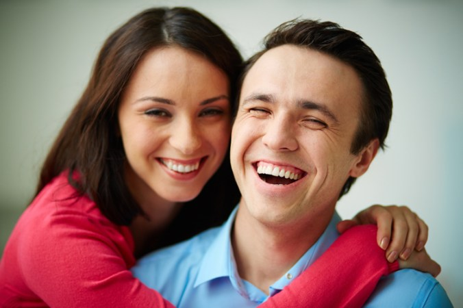 Portrait of amorous young woman embracing her happy husband