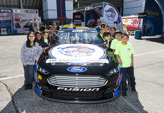 Students from Our Lady of Perpetual Help Catholic School with the No. 16 car