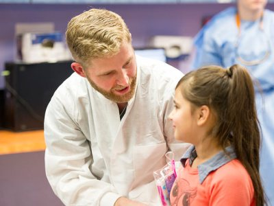 Pediatric dentistry resident Dr. Benjamin Curtis discusses with his young patient what will soon happen with her teeth.