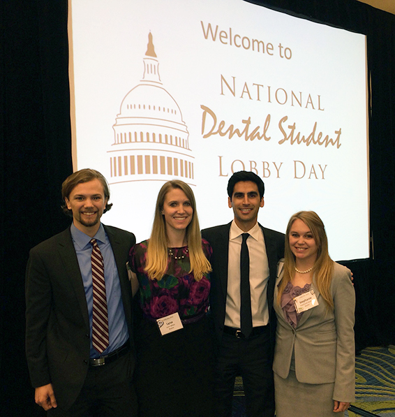 TAMBCD attendees in front of a sign depicting National Dental Student Lobby Day