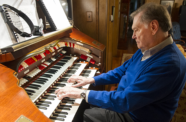 Dr. Bill Hanson, '61, plays the theater organ in the living room of his living room, outfitted with speakers to ensure optimal acoustics.