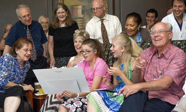 Family, friends and co-workers look at an old photo given to Dr. Dean Hudson, right, during his June 30 retirement reception.