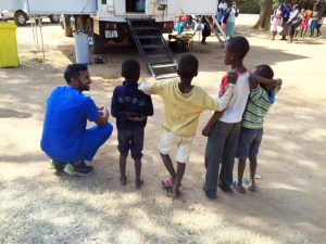 A dental student kneels next to some young children in Zambia.