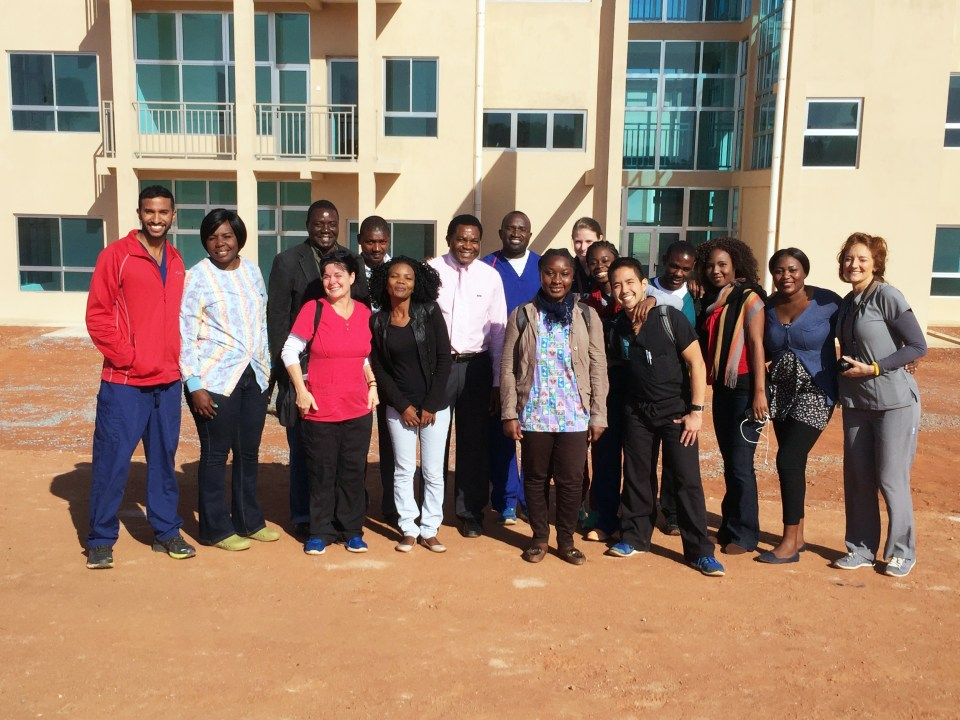 A group of people smile in front of Copperbelt University School of Medicine's new dental campus.