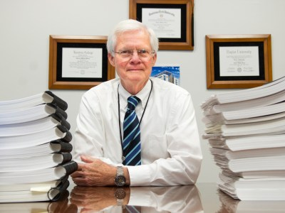 Dr. Charles Berry sits amid stacks of accreditation self study papers