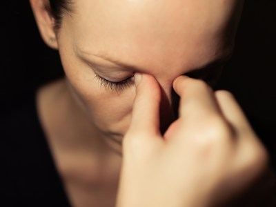 Woman holding her hand to her face