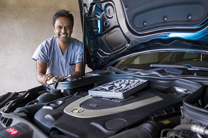 Photo illustration: Dr. Dru Belur with a car engine and tools.