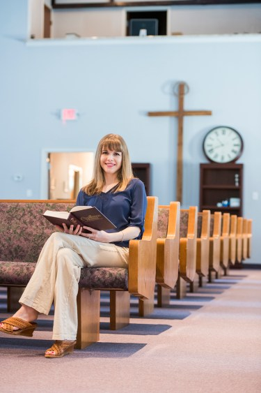 Ashley Lamb in a church pew with a hymnal