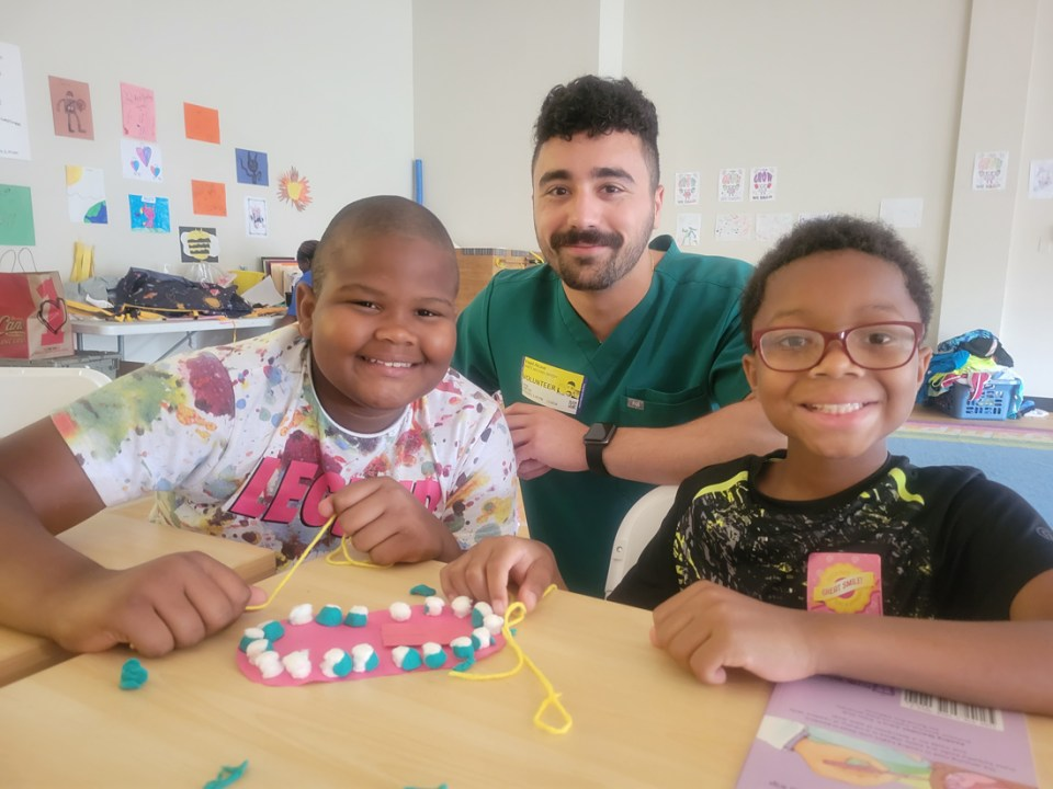Children learn about proper flossing technique with the help of dental student James Needy.