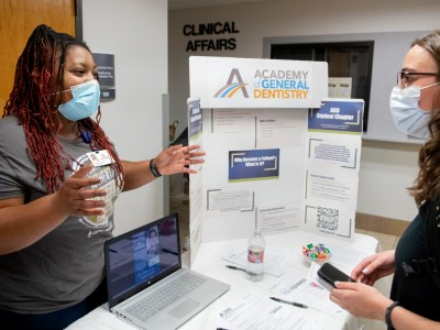 """Fourth-year dental student Akeira """"Cookie"""" Warner shares information with a new student during the student organization fair."""