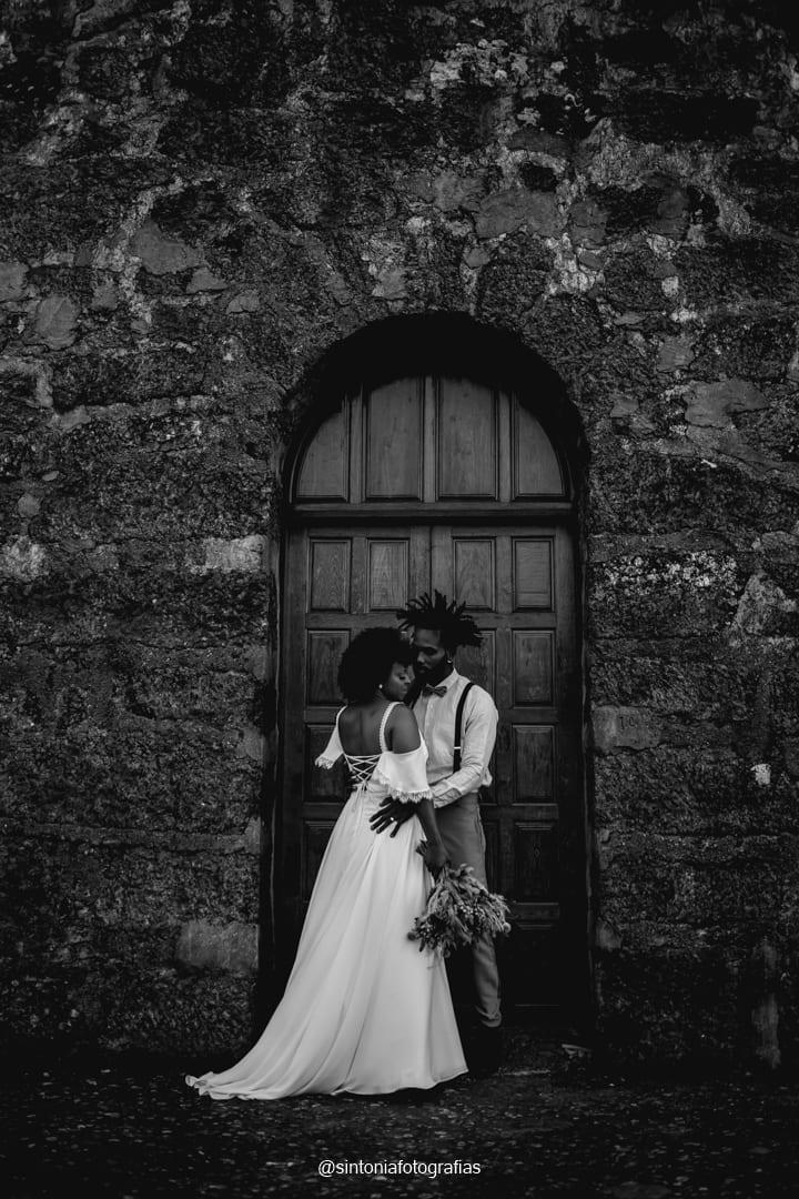 casal de noivos na porta da igreja se abraçando