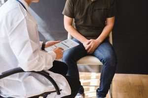 man sitting with hands in lap while talking to doctor