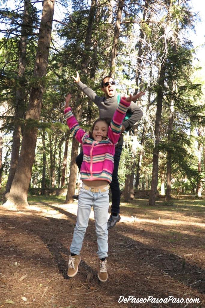 Padre e hija saltando en el bosque