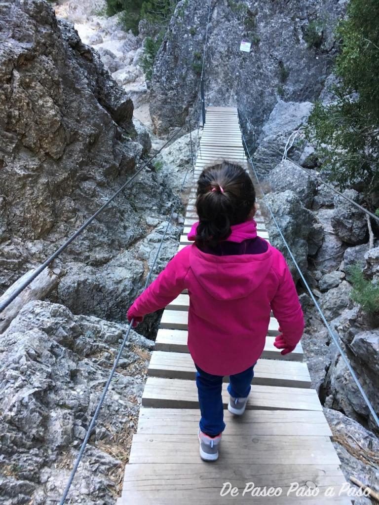niña cruzando puente colgante de madera sobre rocas