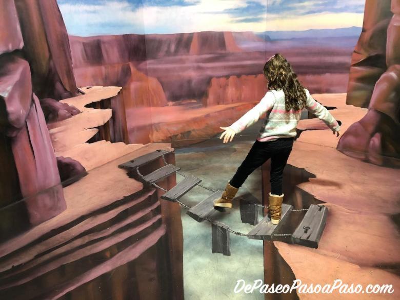 Niña simulando que realiza equilibrio para no caer en acantilado en museo de ilusiones Barcelona