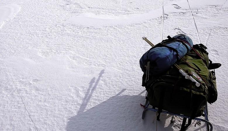 mochila y bastones nieve en paisaje nevado