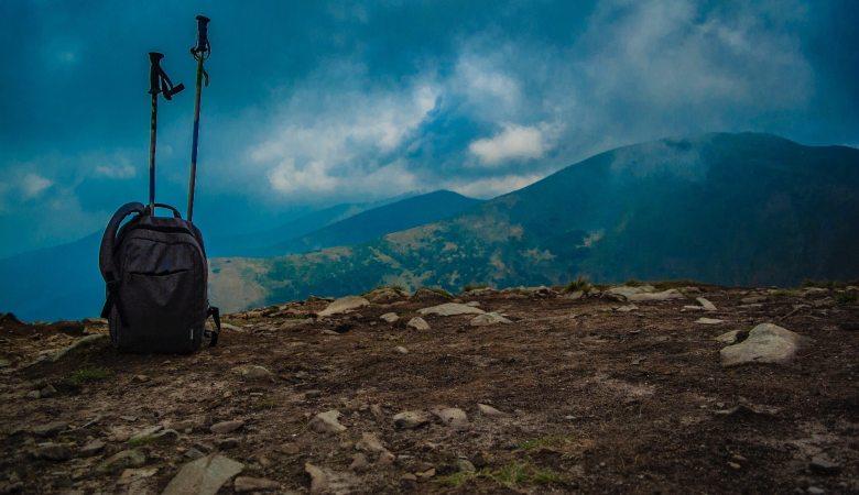 mochila y bastones trekking en lo alto de montaña
