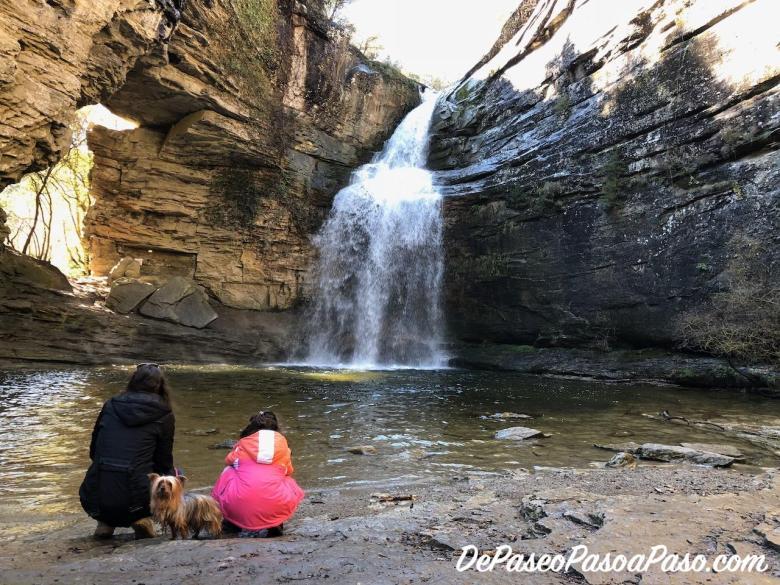 Madre, hija y mascota observando el salto de agua