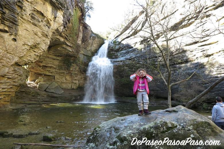 niña sobre una roca con el salto de agua detrás