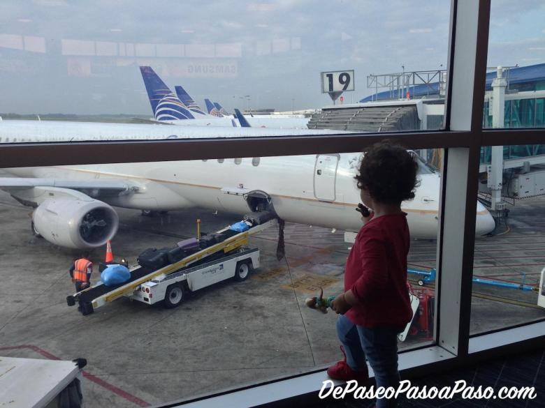 Niña mirando aviones por ventana en aeropuerto
