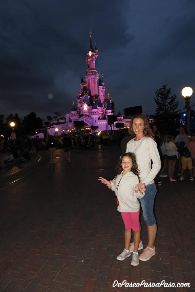 Madre e hija frente a castillo de Disneyland Park en la noche