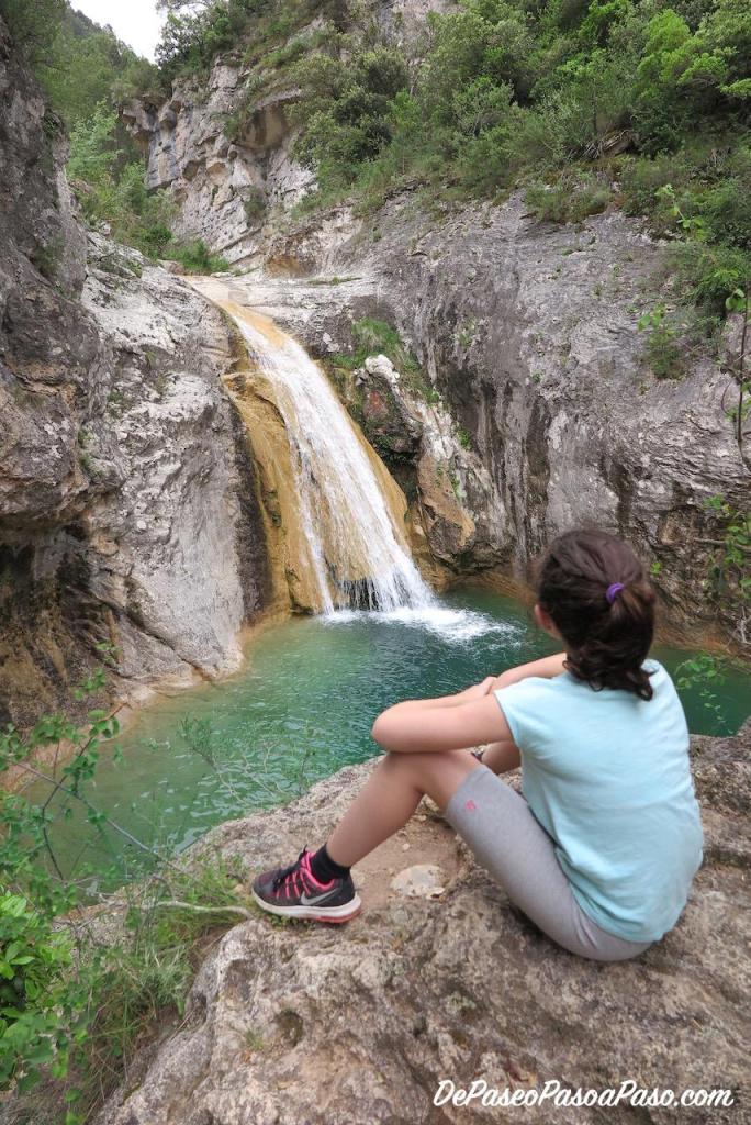 niña sentada en la roca contemplando el salto de agua La Gorgina