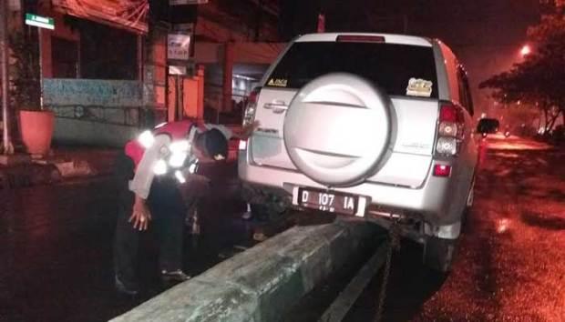 Mobil ini nyangkut di separator Jalan Margonda. Diduga sopir hilang kendali.