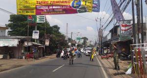 Satpol PP Kota Depok menurunkan spanduk liar di Jalan Raya Sawangan.