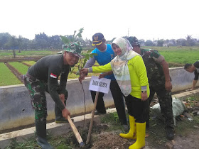 Komandan Kodim 0508/Depok Letkol Inf. Iskandarmanto menanam pohon bersama Kabid SDA Dinas PUPR Citra Indah Yulianti.