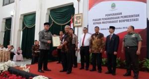 Kepala Disdukcapil Kota Depok, Misbahul Munir menerima penghargaan dari Plt Gubernur Jawa Barat.